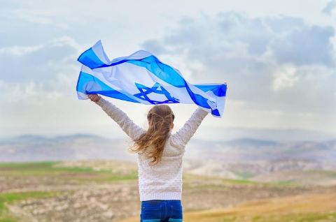 A girl holds an Israeli flag