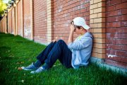 Sad teengage boy sitting against a wall